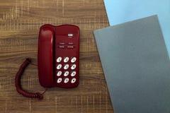 Κόκκινοι τηλέφωνο και σωρός των φακέλλων σε έναν ξύλινο πίνακα στοκ εικόνες