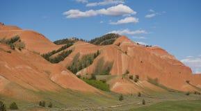 Κόκκινοι λόφοι που ανθίζουν με τις πράσινες χλόες και τα άσπρα σύννεφα που επιπλέουν ανωτέρω στοκ εικόνα