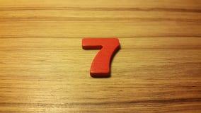 Κόκκινος αριθμός 7 στο ξύλινο υπόβαθρο Στοκ Φωτογραφία