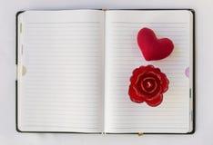 Κόκκινος αυξήθηκε και καρδιά στο κενό βιβλίο σημειώσεων στοκ φωτογραφίες