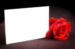 Κόκκινος αυξήθηκε και κενή κάρτα δώρων για το κείμενο στο παλαιό ξύλινο υπόβαθρο Στοκ Εικόνες