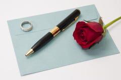 Κόκκινος αυξήθηκε και μαύρο μολύβι με το δαχτυλίδι αρραβώνων στο μπλε envel Στοκ Εικόνα