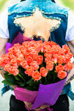 κόκκινος αυξήθηκε Κρύψιμο ατόμων πίσω από μια ανθοδέσμη των λουλουδιών Στοκ εικόνα με δικαίωμα ελεύθερης χρήσης