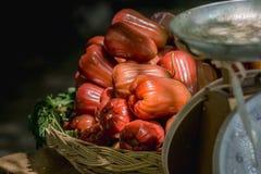Κόκκινος αυξήθηκε μήλο τοποθετείται σε ένα κίτρινο καλάθι ινδικού καλάμου Στοκ φωτογραφίες με δικαίωμα ελεύθερης χρήσης