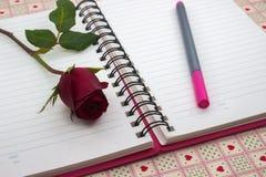 Κόκκινος αυξήθηκε με τη σημείωση και το μολύβι Στοκ φωτογραφία με δικαίωμα ελεύθερης χρήσης