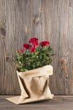Κόκκινος αυξήθηκε λουλούδια paper-bag σε ένα ξύλινο υπόβαθρο Στοκ Φωτογραφίες