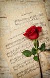 Κόκκινος αυξήθηκε λουλούδι και η εκλεκτής ποιότητας μουσική σημειώνει το φύλλο Στοκ εικόνες με δικαίωμα ελεύθερης χρήσης
