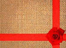 Κόκκινος αυξήθηκε στο υπόβαθρο σύστασης λινού με την κόκκινη κορδέλλα Στοκ φωτογραφία με δικαίωμα ελεύθερης χρήσης