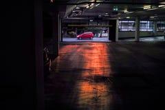 Κόκκινος αυτοκινήτων εσωτερικός υπαίθριος σταθμός αυτοκινήτων υπεραγορών οδήγησης προηγούμενος στο ηλιοβασίλεμα Στοκ εικόνα με δικαίωμα ελεύθερης χρήσης