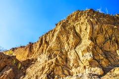 Κόκκινος βράχος απότομων βράχων αργίλου, υπόβαθρο ουρανού Στοκ εικόνα με δικαίωμα ελεύθερης χρήσης