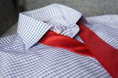 Κόκκινος δεσμός στο άσπρο μπλε πουκάμισο στοκ φωτογραφία με δικαίωμα ελεύθερης χρήσης