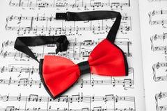 Κόκκινος δεσμός τόξων στο φύλλο μουσικής στοκ φωτογραφία