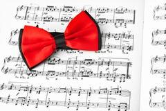Κόκκινος δεσμός τόξων στο φύλλο μουσικής στοκ εικόνες