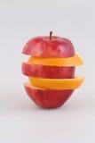 Κόκκινος - εύγευστος και ένα πορτοκάλι τεμαχίζει σε ένα άσπρο υπόβαθρο Στοκ εικόνες με δικαίωμα ελεύθερης χρήσης