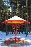 Κόκκινος-κίτρινος πάγκος με μια στρογγυλή στέγη στο υπόβαθρο του δάσους Στοκ Φωτογραφία