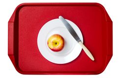 Κόκκινος-κίτρινο μήλο με ένα μαχαίρι σε ένα άσπρο πιάτο ενάντια στο κόκκινο Στοκ φωτογραφία με δικαίωμα ελεύθερης χρήσης