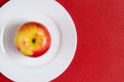 Κόκκινος-κίτρινο μήλο σε ένα άσπρο πιάτο στο κόκκινο κλίμα Στοκ φωτογραφίες με δικαίωμα ελεύθερης χρήσης