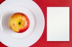 Κόκκινος-κίτρινο μήλο σε ένα άσπρο πιάτο στο κόκκινο κλίμα Στοκ φωτογραφία με δικαίωμα ελεύθερης χρήσης