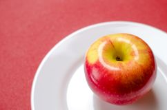 Κόκκινος-κίτρινο μήλο σε ένα άσπρο πιάτο στο κόκκινο κλίμα Στοκ Φωτογραφίες