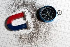 Κόκκινος και μπλε πεταλοειδής μαγνήτης ή φυσική μαγνητικός και πυξίδα με το μαγνητικό πεδίο σκονών σιδήρου στο υπόβαθρο γραφικών  στοκ φωτογραφία με δικαίωμα ελεύθερης χρήσης