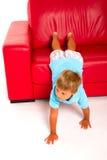 κόκκινος καναπές αγοριών Στοκ Εικόνες