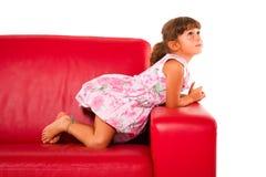 κόκκινος καναπές κοριτσιών Στοκ Φωτογραφίες