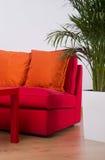 Κόκκινος καναπές με τα πορτοκαλιά μαξιλάρια Στοκ εικόνες με δικαίωμα ελεύθερης χρήσης