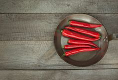 Κόκκινος - καυτά πιπέρια και τηγάνι τσίλι στον εκλεκτής ποιότητας ξύλινο πίνακα Τοπ άποψη με το διάστημα αντιγράφων Στοκ εικόνες με δικαίωμα ελεύθερης χρήσης