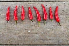 Κόκκινος - καυτά πιπέρια τσίλι στον ξύλινο πίνακα Στοκ Φωτογραφίες