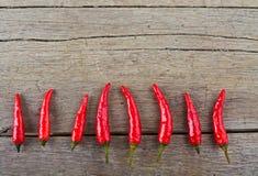 Κόκκινος - καυτά πιπέρια τσίλι στον ξύλινο πίνακα Στοκ Εικόνες