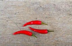 Κόκκινος - καυτά πιπέρια τσίλι στον ξύλινο πίνακα Στοκ Εικόνα
