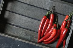 Κόκκινος - καυτά πιπέρια τσίλι στο παλαιό ξύλινο υπόβαθρο στοκ φωτογραφία