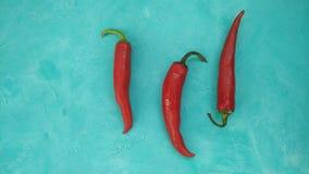 Κόκκινος - καυτά πιπέρια τσίλι στο υπόβαθρο κιρκιριών Στοκ Φωτογραφία