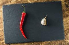 Κόκκινος - καυτά πιπέρι και σκόρδο διαγώνια στα πλαίσια της πλάκας Στοκ Εικόνες