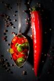 Κόκκινος - καυτό peperoni πιπεριών με το πιπέρι στο μαύρο υπόβαθρο πλακών Στοκ Εικόνα