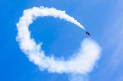 Κόκκινος μαχητής αγώνα με τον άσπρο καπνό κύκλων πίσω στο μπλε ουρανό Στοκ Εικόνες