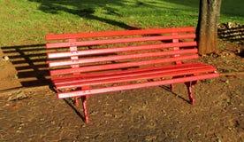 Κόκκινος ξύλινος πάγκος στο πάρκο Στοκ Φωτογραφίες