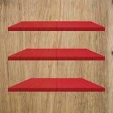 3 κόκκινος ξύλινος πίνακας ραφιών στον ξύλινο τοίχο Στοκ Εικόνες