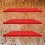 3 κόκκινος ξύλινος πίνακας ραφιών στον παλαιό τοίχο τσιμέντου Στοκ εικόνες με δικαίωμα ελεύθερης χρήσης