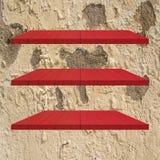 3 κόκκινος ξύλινος πίνακας ραφιών στον παλαιό τοίχο τσιμέντου Στοκ Φωτογραφία