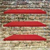 3 κόκκινος ξύλινος πίνακας ραφιών στον παλαιό τουβλότοιχο Στοκ φωτογραφία με δικαίωμα ελεύθερης χρήσης