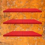 3 κόκκινος ξύλινος πίνακας ραφιών στον πορτοκαλή τοίχο τσιμέντου Στοκ φωτογραφίες με δικαίωμα ελεύθερης χρήσης