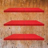 3 κόκκινος ξύλινος πίνακας ραφιών στον τοίχο τσιμέντου Στοκ Φωτογραφία