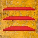 3 κόκκινος ξύλινος πίνακας ραφιών στο κίτρινο τσιμέντο Στοκ Φωτογραφίες