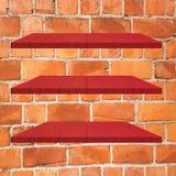 3 κόκκινος ξύλινος πίνακας ραφιών στο τουβλότοιχο Στοκ Εικόνες