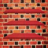 3 κόκκινος ξύλινος πίνακας ραφιών στο τουβλότοιχο Στοκ εικόνες με δικαίωμα ελεύθερης χρήσης