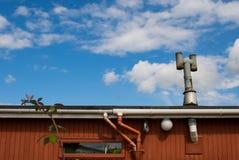Κόκκινος ξύλινος τοίχος ενάντια στο μπλε ουρανό Στοκ Εικόνες