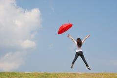 κόκκινος ουρανός άλματος στη γυναίκα ομπρελών Στοκ φωτογραφία με δικαίωμα ελεύθερης χρήσης