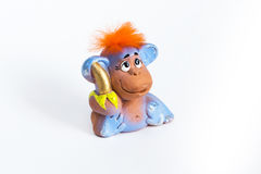 Κόκκινος πίθηκος τρίχας με την μπανάνα στο άσπρο υπόβαθρο Στοκ εικόνες με δικαίωμα ελεύθερης χρήσης