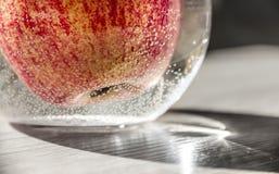 Κόκκινος πορτοκαλής κίτρινος της Apple σε ένα βάζο με το νερό στις αεροφυσαλίδες οριζόντιες στη μακροεντολή κινηματογραφήσεων σε  Στοκ εικόνα με δικαίωμα ελεύθερης χρήσης